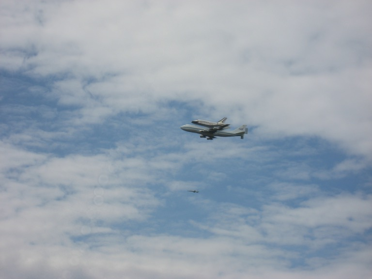 A side view of Discovery, the transport plane, and the escort.