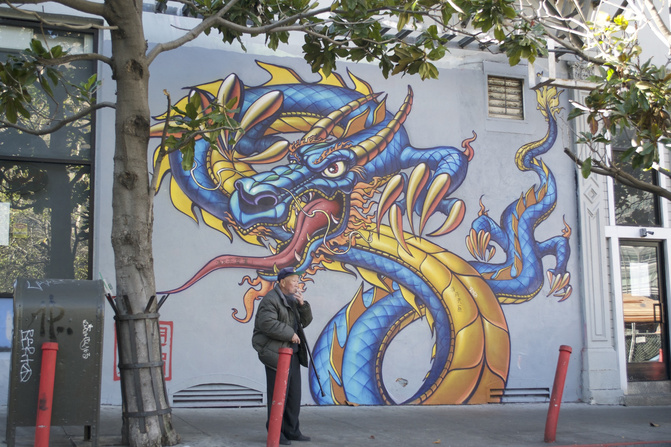 An old smoking man sands in front of a mural of a blue dragon.