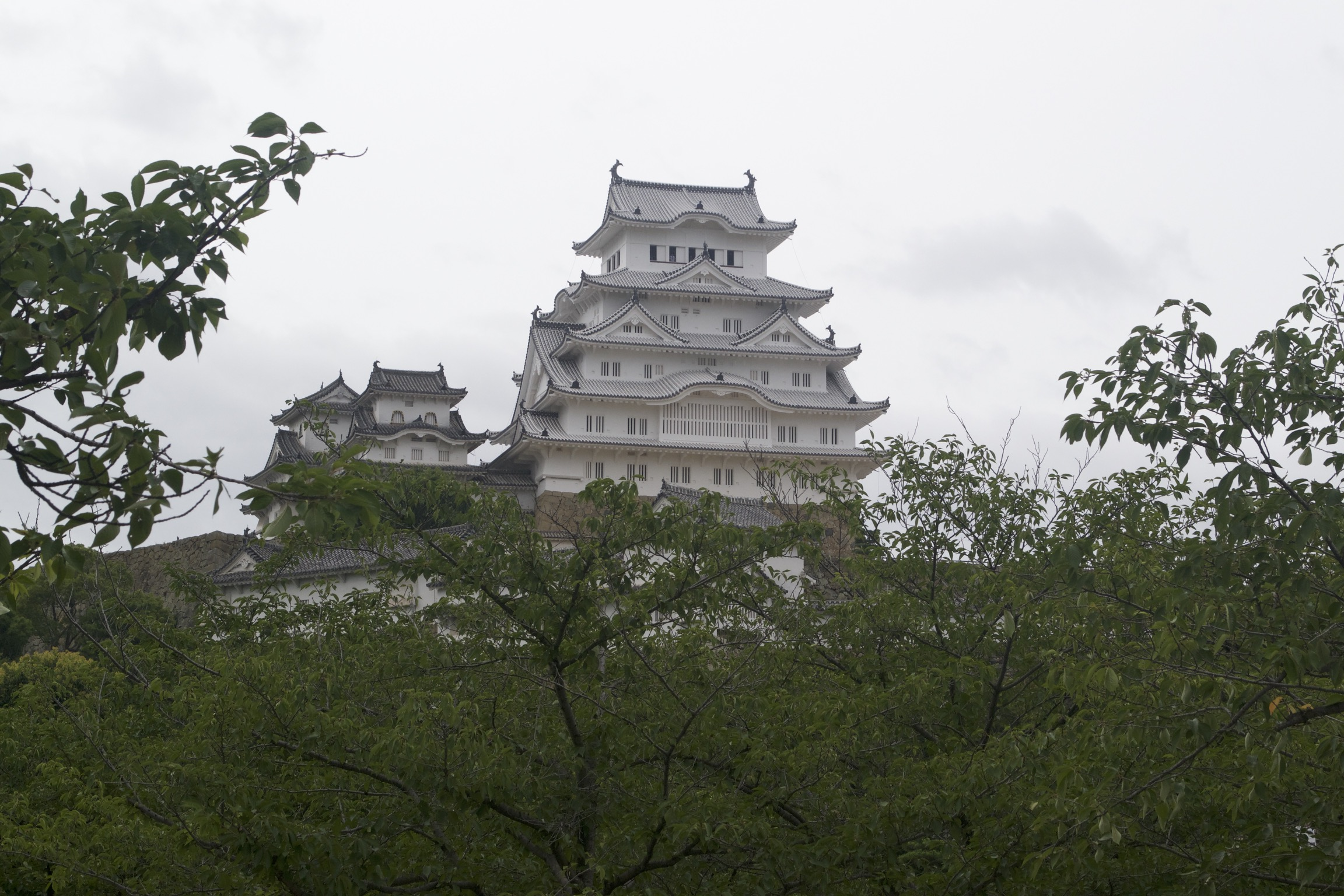 A black and white tiered castle stands against a gray sky.