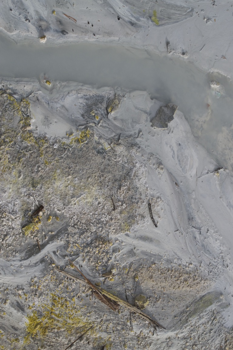 A closeup of the opaque gray water and yellow sulfur deposits.
