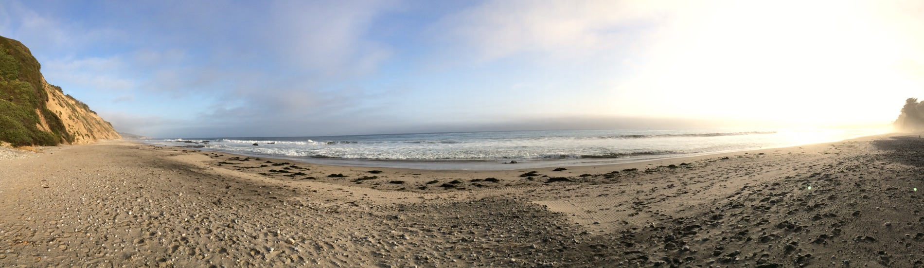 A panorama of an empty beach---blue skies at one end, golden at the other.