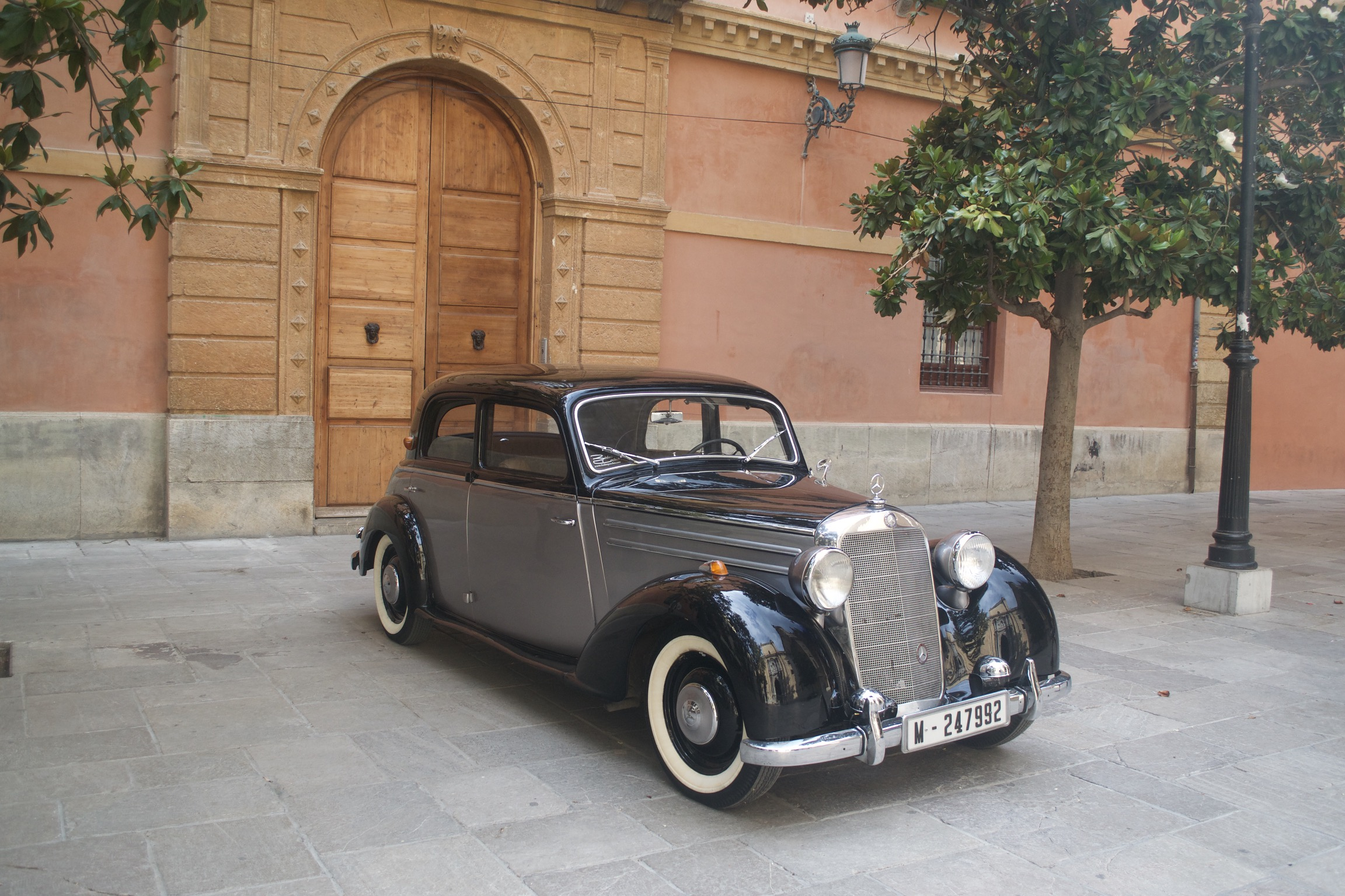 A classic black and gray Mercedes sits in a plaza before a Spanish building's large wooden doors.