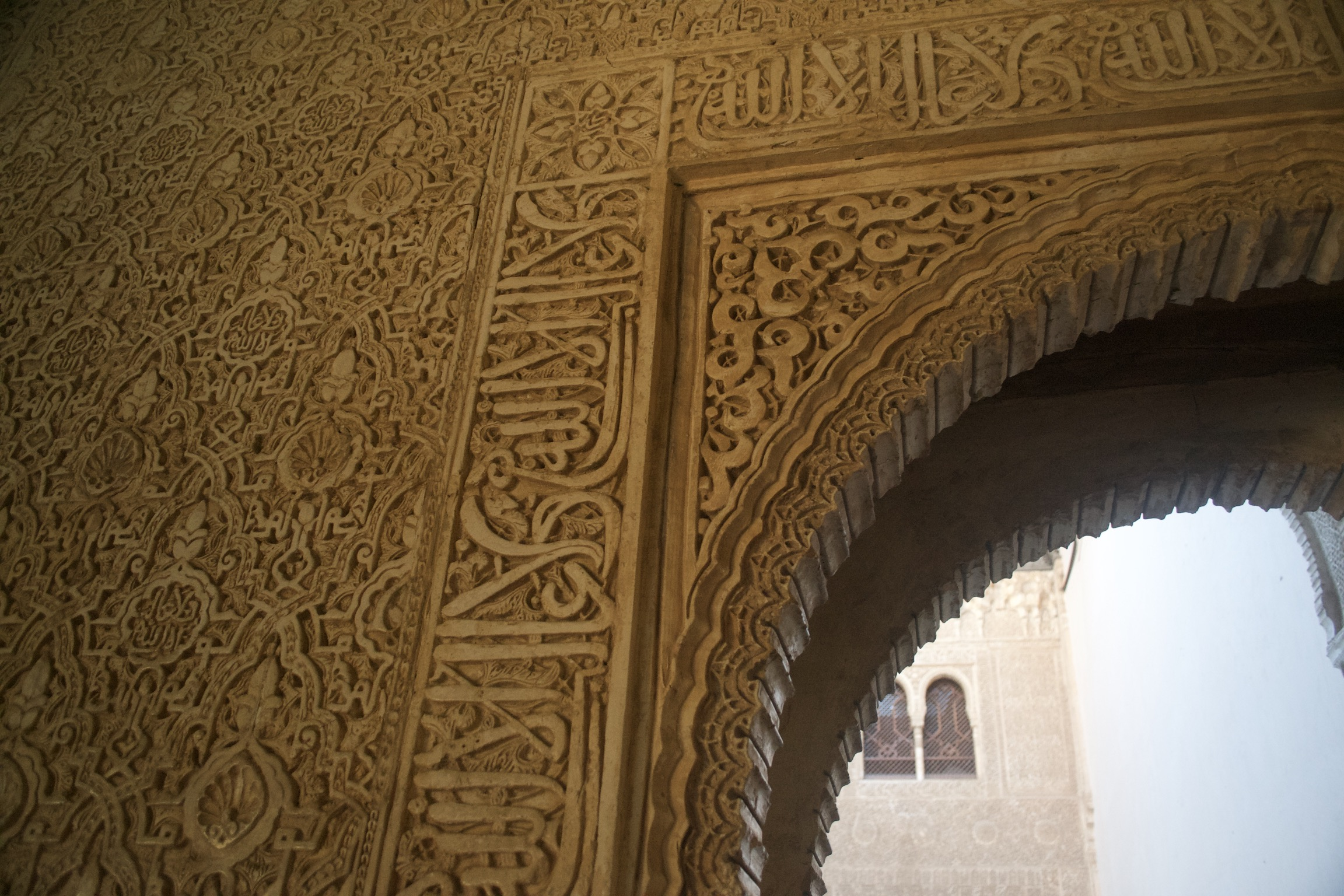 Details of the intricate designs and inscriptions on the wall surrounding an arched doorway.