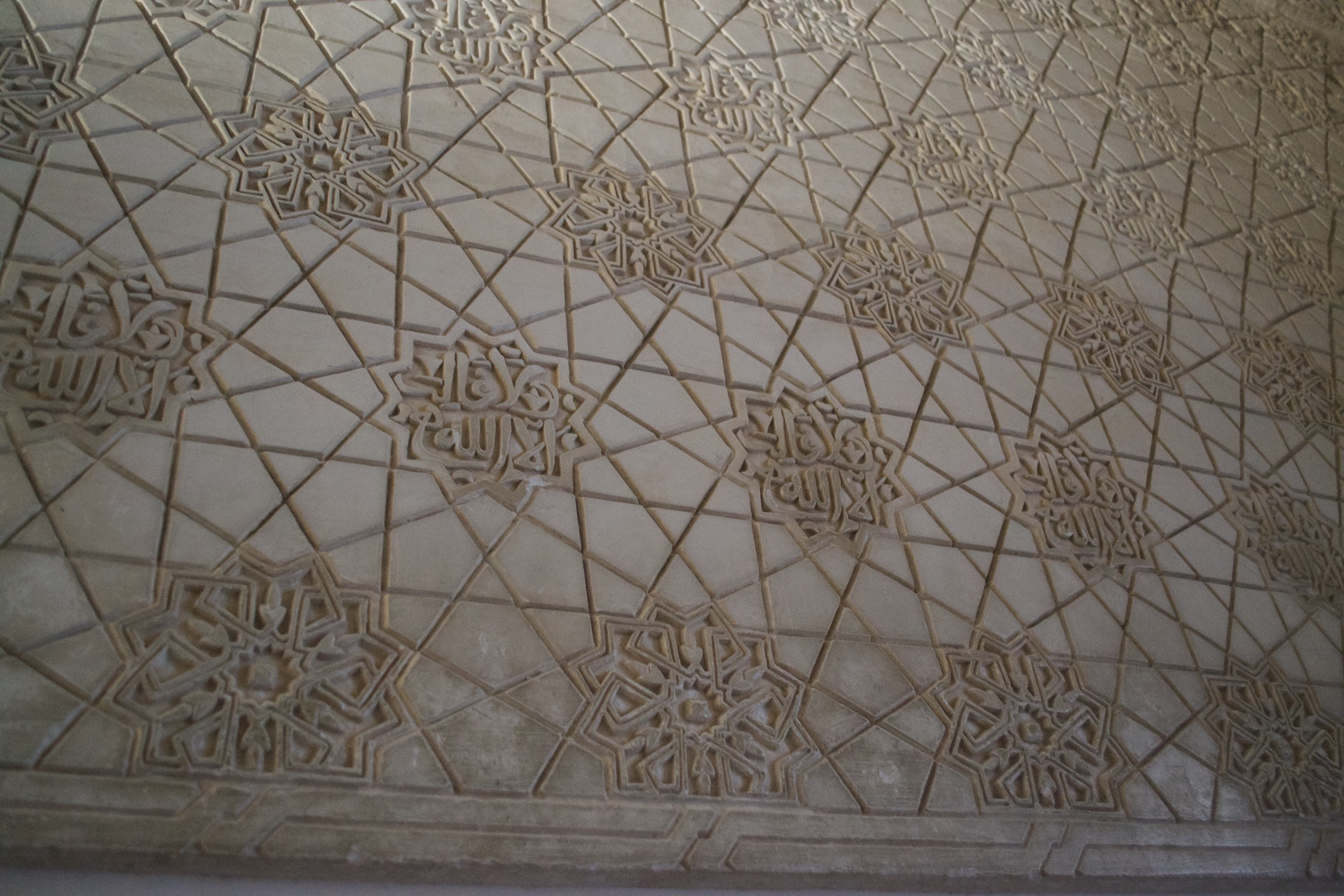 A tesselation of eight-pointed stars and rays emanating from them.  The stars' interiors contain either geometric designs or Arabic inscriptions.