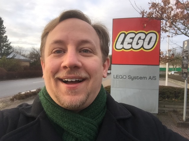 A 30-year-old man with blond hair and beard, smiling widely in front of the red LEGO sign of the LEGO Headquarters.