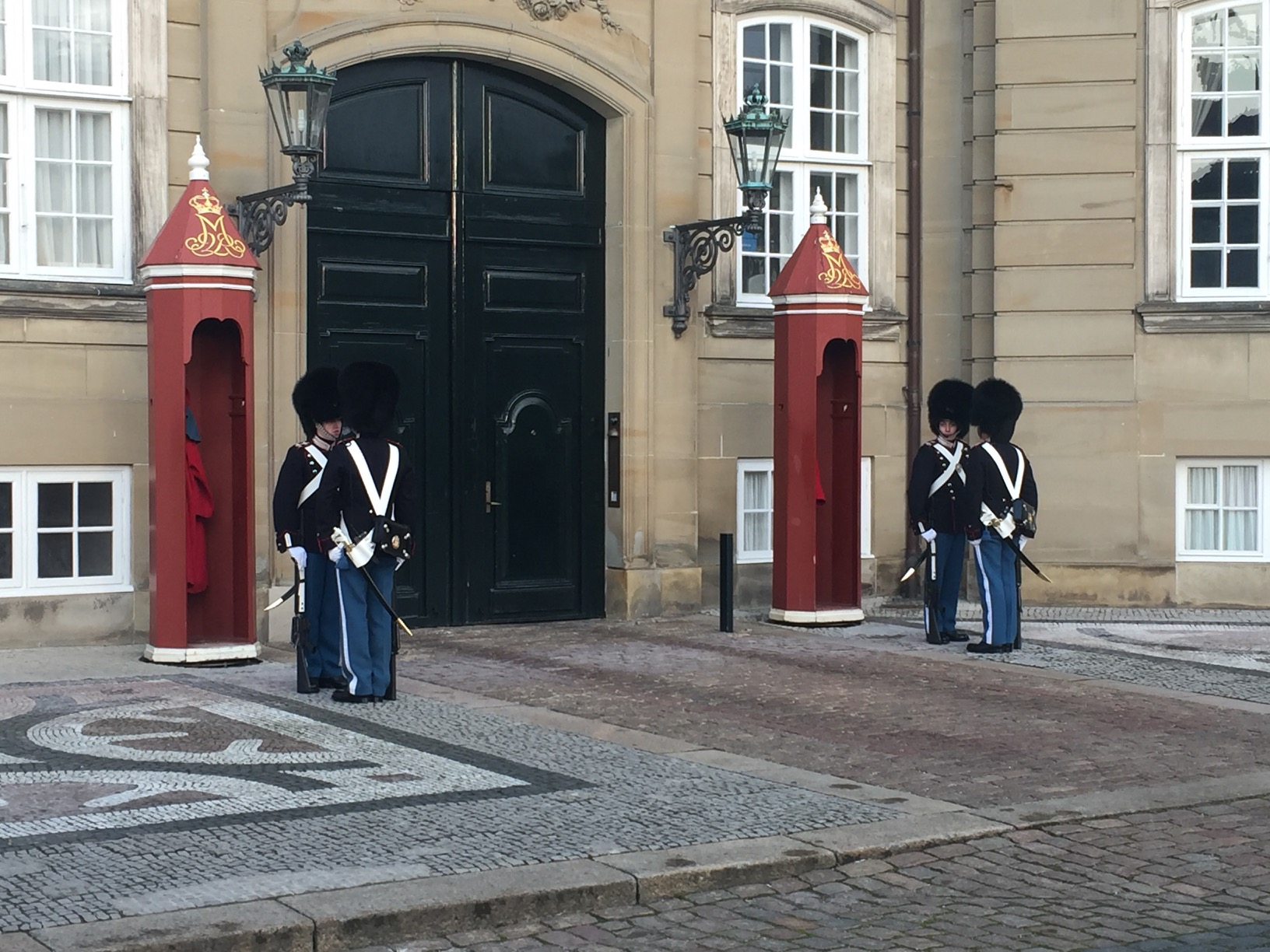 Two pairs of guards dressed in blue pants, black jackets, and tall, furry hats, face one another before two red booths a wide, black doorway into a stone building.