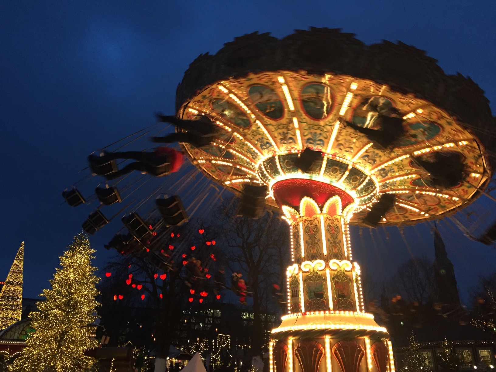 A brightly-lit swing carousel near an illuminated Christmas tree before a dark sky.