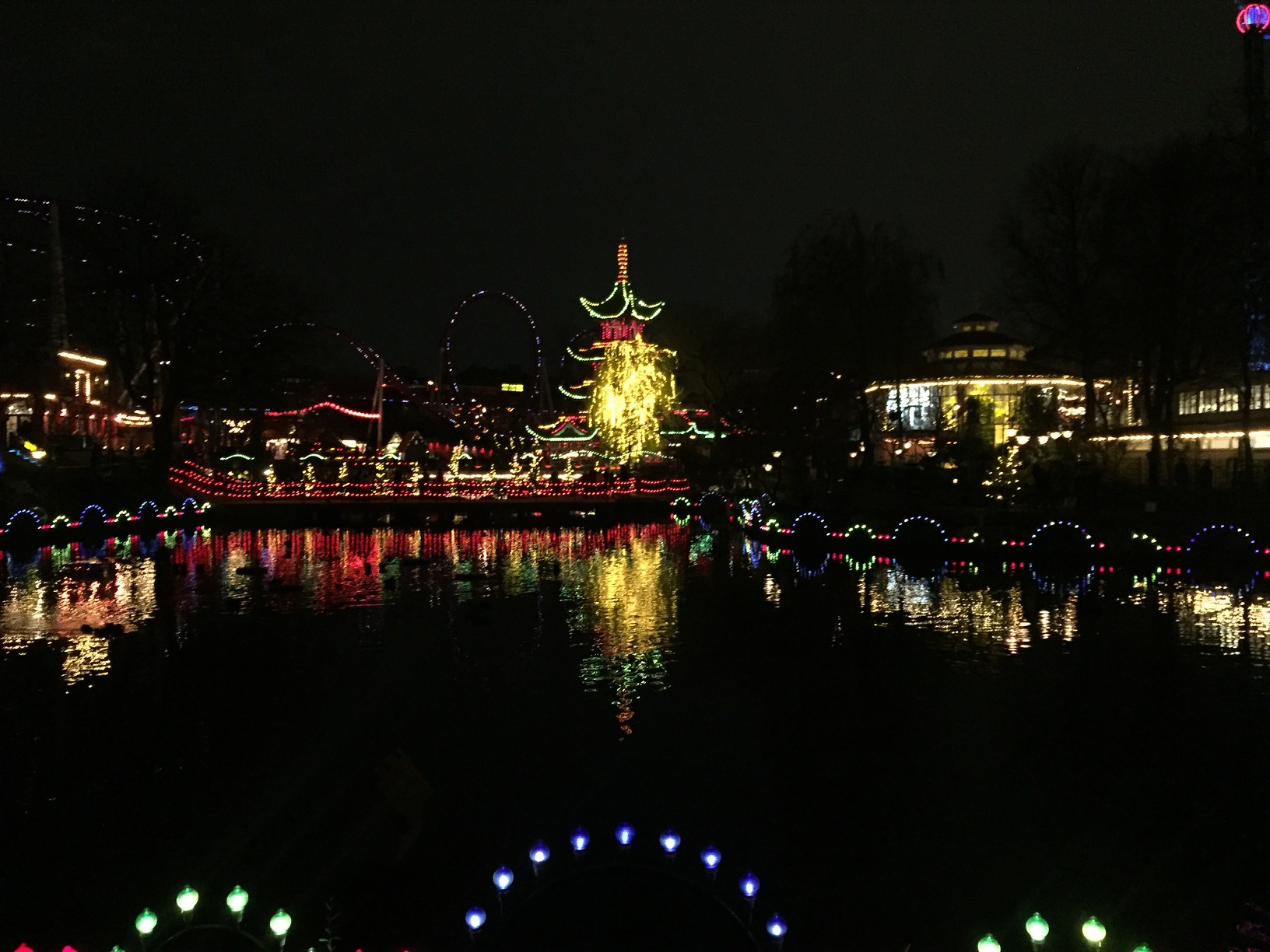 A lake reflects a lit-up amusement park pagoda.