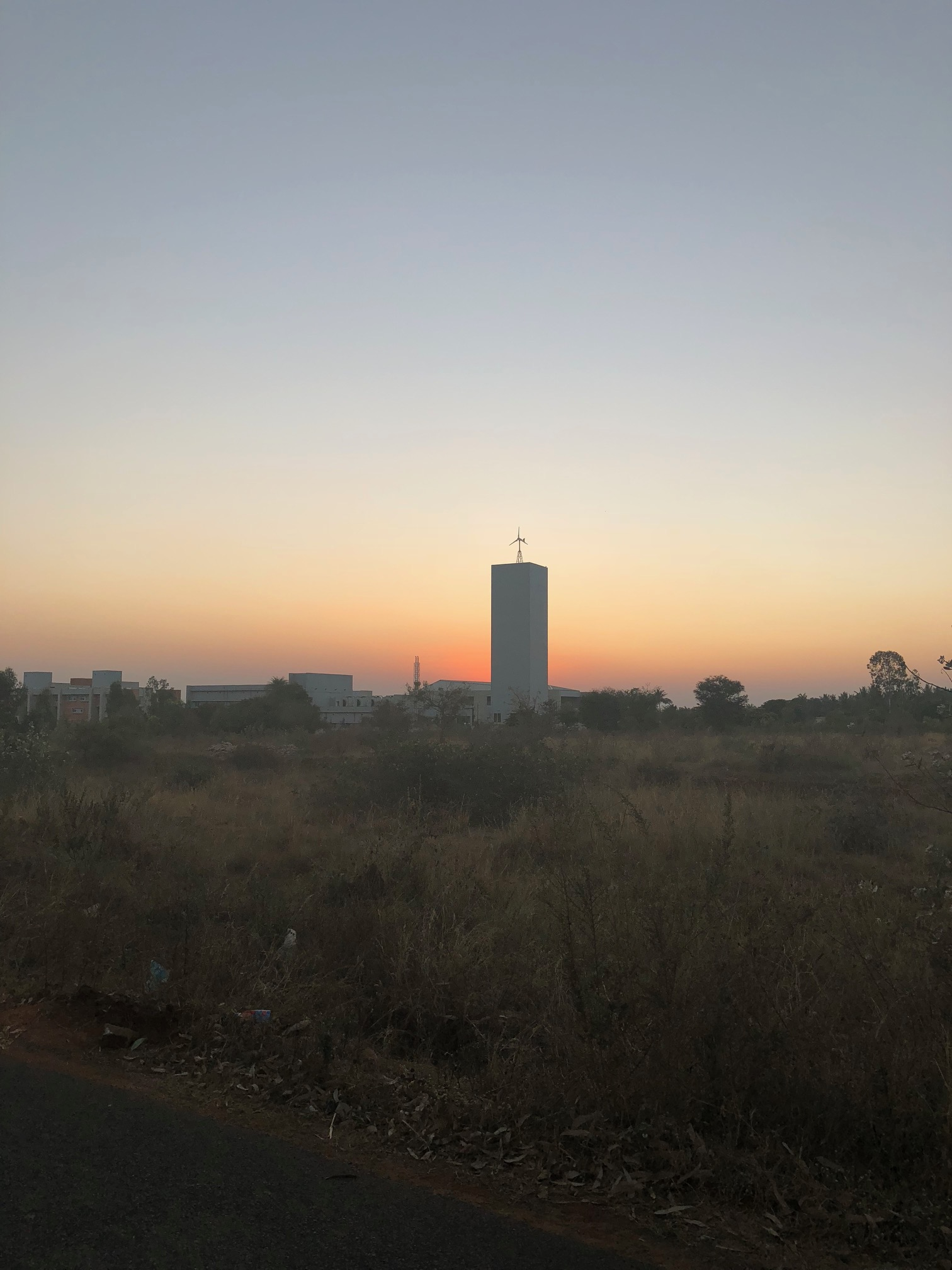 The sunset is blocked by a large, rectangular building that towers over a nearby adjacent campus.