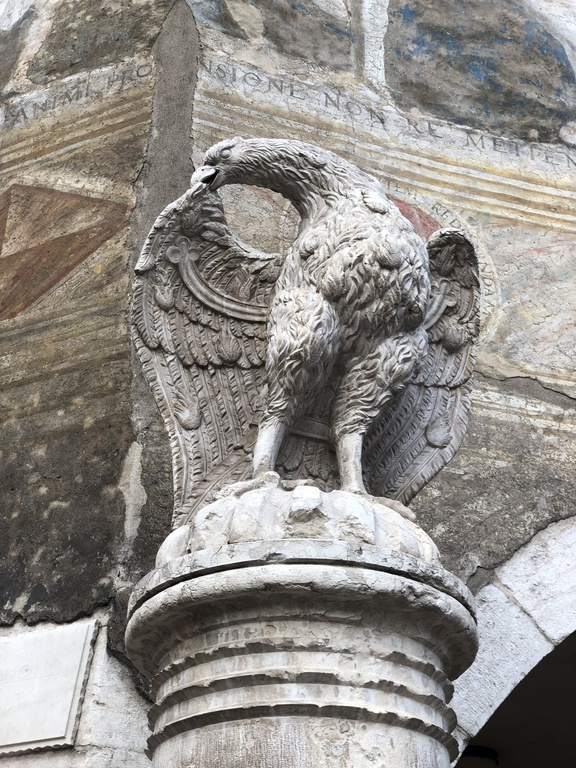 A stone eagle on a pedastal, preening its wings, in front of a dirty fresco.